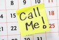 Call me with an exclamation mark written by hand on a yellow sticky paper note and stuck to a wall calendar background Royalty Free Stock Photos