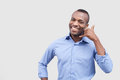 Call me handsome young african man showing a sign and smiling while standing isolated on grey background Royalty Free Stock Image