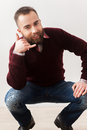 Call me handsome young bearded man showing a sign and smiling while sitting on the floor Stock Images