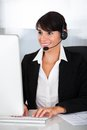 Callcenter employee with headset happy young female wearing in office Stock Photos