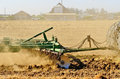 Cally ag a tractor pulls a disc harrow system implement to smooth over a dirt field in preperation for planting in central Stock Photo
