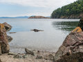 Calm bay water and rocky shore the of a with in the foreground the mountains of other islands in the distance on lopez island in Royalty Free Stock Images
