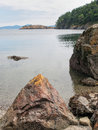 Calm bay water and rocky shore the of a with in the foreground the mountains of other islands in the distance on lopez island in Stock Images