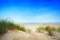Calm beach with dunes and green grass. Tranquil ocean Royalty Free Stock Photo