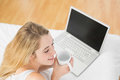 Calm blonde woman holding a cup lying on bed next to her laptop at home Royalty Free Stock Photography
