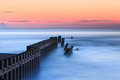Calm blue ocean north carolina an unusually at sunrise in buxton where the coastal engineered groyne interrupts water flow of the Royalty Free Stock Photography