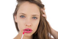 Calm brunette model applying pink gloss on her lips white background Stock Image