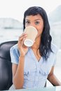 Calm businesswoman drinking coffee in office Royalty Free Stock Photography