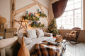 Calm image of interior modern home living room decorated christmas tree and gifts, sofa, table covered with blanket. Royalty Free Stock Photo