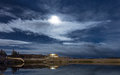 A calm night by the lake in city of reykjavik iceland with full moon hiding behind clouds Royalty Free Stock Photo