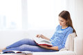 Calm teenage girl reading book on couch Royalty Free Stock Photo