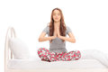 Calm young woman in pajamas meditating on a bed seated isolated white background Royalty Free Stock Photography