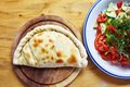 Calzone and salad c close up closed italian pizza on the wood table Stock Image