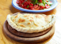 Calzone and salad a close up closed italian pizza on the wood table Royalty Free Stock Image