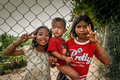 Cambodian children siblings posing for a photo from behind a fence near the killing fields Royalty Free Stock Photo
