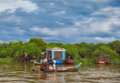 Cambodian women sail on a boat near the fishing village of Tonle Sap Lake