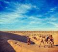 Cameleer camel driver with camels in dunes of thar desert raj vintage retro hipster style travel image rajasthan travel background Royalty Free Stock Images