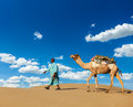 Cameleer camel driver with camels in rajasthan india travel background indian dunes of thar desert jaisalmer Stock Photo