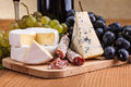 Camembert blue cheese and dry sausage snack macro of with grape cluster Stock Images