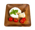 Camembert cheese and fresh cherry tomatoes wooden plate with white closeup Stock Photo