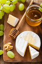 Camembert cheese with grapes honey and nuts on wooden background Royalty Free Stock Photography
