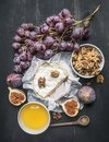 Camembert cheese on old dark wooden table with a bowl of walnuts, honey, a vintage table knife, cut figs and branch of grapes, top Royalty Free Stock Photo