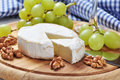 Camembert on wooden cutting board with grape and walnut closeup Royalty Free Stock Images