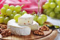 Camembert on wooden cutting board with grape and walnut closeup Royalty Free Stock Photography
