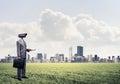 Camera headed man standing on green grass against modern citysca