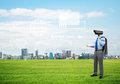 Camera headed man standing on green grass against modern cityscape