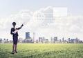 Camera headed woman standing on green grass against modern citys
