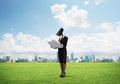 Camera headed woman standing on green grass against modern cityscape