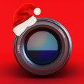 Camera lens with santa hat on a red background Royalty Free Stock Images