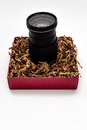 Camera zoom lens upright in gift box a standing a filled with brown shredded paper Royalty Free Stock Image