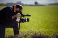 Cameraman a with a professional camcorder in a green idyllic field Royalty Free Stock Images