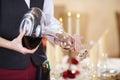 Cameriera di bar pouring red wine in bicchiere di vino Fotografie Stock Libere da Diritti