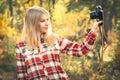 A camisa de manta vestindo da jovem mulher com a câmera retro da foto que toma o selfie disparou em exterior Fotos de Stock Royalty Free