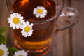 Camomile tea glass cup of with flowers on vintage wood table Royalty Free Stock Photo