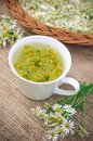 Camomile tea in white cup on wooden surface Stock Photos