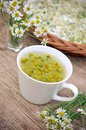 Camomile tea in white cup on wooden surface Royalty Free Stock Image