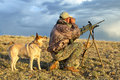 Camouflaged hunter with rifle and tracking dog Royalty Free Stock Photo