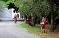 Camouflaged leaf blowers working in park singapore july four foreign workers clear leaves from near the orchard road entrance at Stock Photos