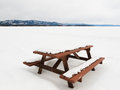 Camp table benches and snowy frozen lake landscape closed for the season beautiful lakeside campsite with wooden burried in snow Royalty Free Stock Photo