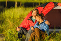 Camping couple enjoying sunset hugging and the Stock Photos