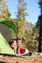 Camping couple in tent romantic looking at view forest campers smiling happy outdoors forest multiracial having fun Royalty Free Stock Photography