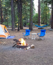 Campsite in the woods with a tent,two chairs, hammock and a burning firepit. Royalty Free Stock Photo