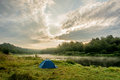 Camping tent on the bank of the river volga blue early in morning with красвыми clouds and their reflection in Royalty Free Stock Image