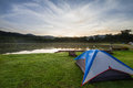 Camping tent on green grass beside lake with foggy over forest during sunrise Royalty Free Stock Photo