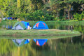 Camping tent on a lake with reflections in the moutain Stock Photo