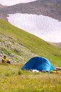 Camping tent in mountains with man hiker sitting on grass and glacier hillside on background Royalty Free Stock Photos